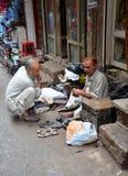 补鞋匠在被围住的城市拉合尔,巴基斯坦修理鞋子 免版税图库摄影
