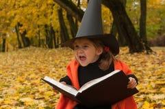 代表一个邪恶的巫婆的一个小女孩的万圣夜照片在黑和橙色和拿着穿戴了一本不可思议的书 免版税图库摄影