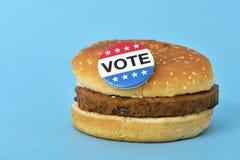 表决在汉堡包的别针按钮 库存照片
