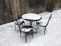 表和三把椅子在雪 免版税图库摄影