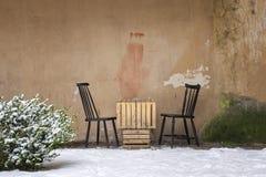 表和两把椅子在墙壁附近 库存照片