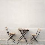 表和两把椅子在墙壁附近 免版税库存照片