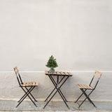 表和两把椅子在墙壁附近 图库摄影