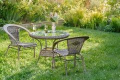 表和两把椅子在庭院里 库存照片