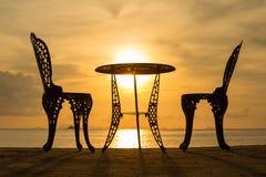 表和两把椅子在日落 库存照片