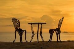 表和两把椅子在日落 免版税库存照片