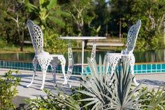 表和两把椅子在水池旁边 免版税库存图片