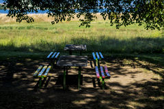 表和五颜六色的长凳在树下 免版税库存照片