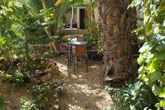表和四把椅子在庭院里 免版税库存图片
