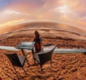 表和椅子在一个热带海滩有日落视图 免版税库存图片