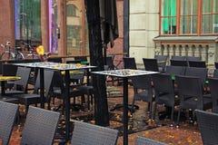 表和椅子在一个街道咖啡馆在雨以后在秋天 免版税库存照片