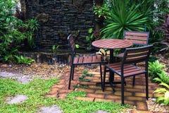表和椅子在美丽的室外庭院里设置了 免版税库存照片