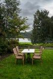 表和椅子在草坪由湖在冷的秋天天 库存图片