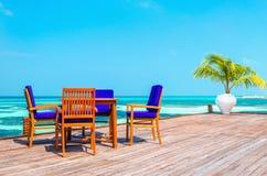 表和椅子在高跷的一家木餐馆在天蓝色的水和蓝天背景  库存图片