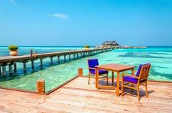 表和椅子在高跷的一家木餐馆在天蓝色的水和蓝天背景  免版税库存照片