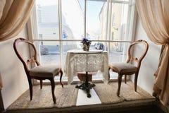 表和椅子由窗口在空的咖啡馆 免版税库存照片