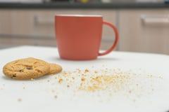 表在家与杯、巧克力饼干和面包屑,休闲生活方式概念,软的焦点 免版税库存照片
