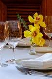 表在有一朵黄色兰花的餐馆 免版税库存图片