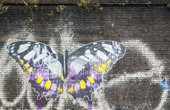 代表在砖墙上的艺术品一只大蝴蝶 免版税图库摄影