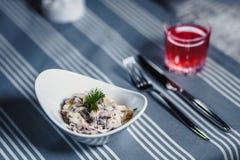 表在餐馆 在桌上是在一块白色板材,刀子,叉子,一块玻璃的沙拉用红色汁液 在桌上 库存照片