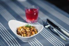表在餐馆 在桌上是在一块白色板材,刀子,叉子,一块玻璃的沙拉用红色汁液 在桌上 图库摄影