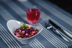 表在餐馆 在桌上是在一块白色板材,刀子,叉子,一块玻璃的沙拉用红色汁液 在桌上 免版税库存图片