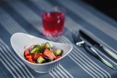 表在餐馆 在桌上是在一块白色板材,刀子,叉子,一块玻璃的沙拉用红色汁液 在桌上 免版税库存照片
