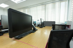 表工作在有黑计算机的办公室 库存图片