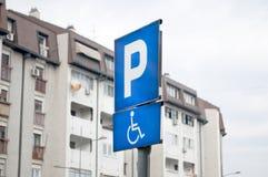 表明一个停车场和一个地方人的交通标志以伤残与汽车 免版税库存照片