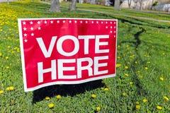 表明一个投票站的地点的这里`表决`标志在Willowick,俄亥俄,在5月2018 primay竞选期间的美国 免版税图库摄影