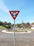 表明前面环形交通枢纽的红色,白色和黑标志 免版税库存图片
