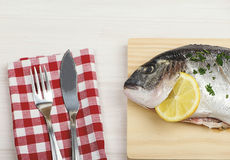 表服务与刀子和叉子与生鱼在一个木板 水平的演播室射击 免版税库存照片