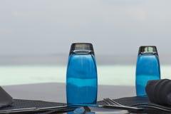 表服务与蓝色杯子在海背景的早餐 免版税库存照片