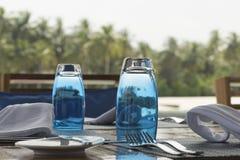 表服务与蓝色杯子在海背景的早餐 免版税库存图片