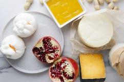 表服务用荷兰扁圆形干酪,普罗卧干酪,乳清干酪,buratta,花生,石榴,鲜美晚餐的蜂蜜 服务的桌顶视图,大量g 免版税图库摄影