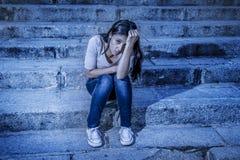 表现主义编辑了画象年轻哀伤和沮丧的妇女或青少年女孩坐孤独在看起来绝望a的街道楼梯 免版税库存照片