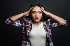表现出震惊年轻西裔美国人的妇女情感户内 免版税图库摄影