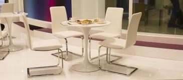 表用咖啡和饼干和四把椅子 免版税库存照片