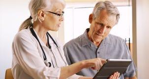 表示资深的医生健康关心年长人患者 免版税图库摄影