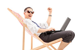 表达年轻的人坐与膝上型计算机的一把椅子和happin 图库摄影