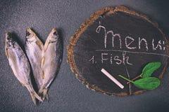 黑表面上的三条干鱼 免版税库存图片
