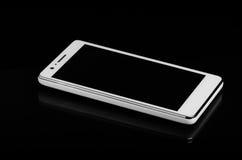 黑表面上的白色巧妙的电话与反射 免版税库存图片