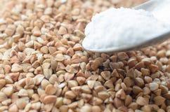 表面和几勺盐上撒布的碎荞麦片 免版税库存照片