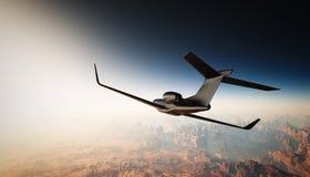 黑表面无光泽的豪华普通设计私人喷气式飞机飞行照片在天空的在地面下 全部背景的峡谷 库存照片