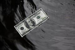 水表面,黑背景上的美元 图库摄影