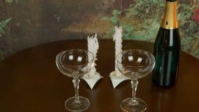 表黑暗的木颜色 倒空二葡萄酒杯 对对光检查照明设备 打击蜡烛 瓶在桌上的香槟酒 股票视频