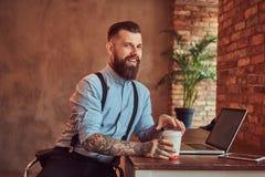 衬衣和悬挂装置的愉快的英俊的被刺字的行家拿着外带的咖啡,当在书桌,运转坐a时 免版税库存图片