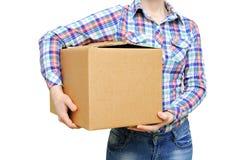 衬衣和牛仔裤的女孩拿着一个大纸板箱 白色孤立 免版税库存图片