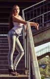衬衣和牛仔裤的美丽的女孩在台阶突出在日落时间 免版税库存图片
