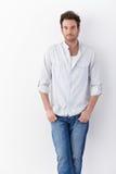 衬衣和牛仔裤的英俊的人 免版税库存图片